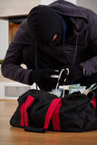 Thief searching bag. A closeup of a thief searching his bag with stolen stuff royalty free stock photos