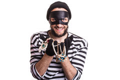 Thief showing stolen jewelry and smiling. Portrait isolated on white background Royalty Free Stock Photo
