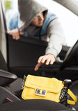 Thief stealing bag from the car. Transportation, crime and ownership concept - thief stealing bag from the car royalty free stock photos