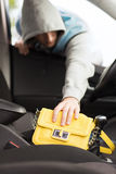 Thief stealing bag from the car. Transportation, crime and ownership concept - thief stealing bag from the car stock images