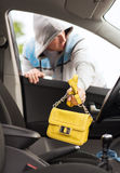 Thief stealing bag from the car. Transportation, crime and ownership concept - thief stealing bag from the car royalty free stock images