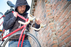 Thief stealing a bike in the city street. Thief stealing a parked bike in the city street Royalty Free Stock Images