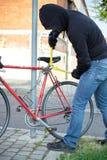 Thief stealing a bike in the city street. Thief stealing a parked bike in the city street Stock Image