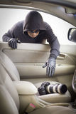 Thief stealing camera  from car Royalty Free Stock Photos
