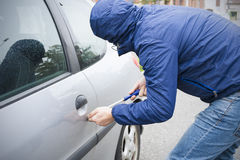 Thief stealing car. Thief stealing automobile car at daylight street in city stock photography