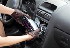 Thief stealing a car radio. Gloved hands of a thief stealing a car radio from the dashboard of a car with the wiring exposed stock images