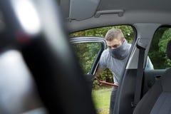 Thief stealing a car Stock Photo