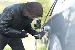 Thief stealing a car. Thief wearing black clothes and leather coat stealing a car Royalty Free Stock Photography
