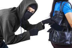 Thief stealing cell phone. Thief stealing a mobile phone from handbag of a woman isolated on white royalty free stock image
