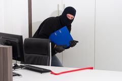 Thief stealing company info Royalty Free Stock Photo