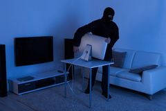 Thief stealing computer monitor from living room. Full length of thief stealing computer monitor from living room royalty free stock image