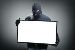 Thief stealing computer monitor stock image