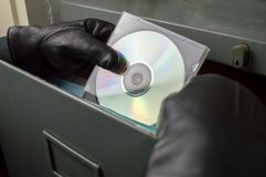 Thief stealing documents in compact disc. Thief stealing in a digitized office files in compact disk stock photography