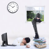 Thief stealing document in office. Male thief with a mask take document through a window while the employee is sleeping Stock Photos