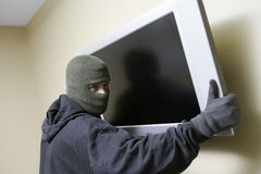 Thief Stealing Flat Screen Television. Thief in balaclava stealing flat screen television from house royalty free stock image