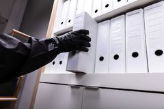 Thief Stealing Folder From Shelf royalty free stock photo