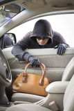 Thief stealing handbag from car. At parking lot stock image
