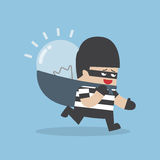 Thief stealing idea bulb and carrying on his back Stock Photography