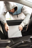 Thief stealing laptop from the car. Transportation, crime and ownership concept - thief stealing laptop from the car stock photo