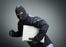 Thief stealing laptop computer. Concept for hacker, hacking, security or insurance stock photography