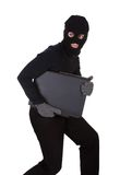 Thief stealing a laptop computer. Thief dressed in black and wearing a balaclava stealing a laptop computer and making a furtive escape isolated on white Royalty Free Stock Image
