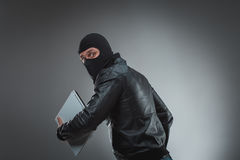 Thief stealing a laptop computer.  on gray background. Studio shot Stock Photos