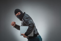 Thief stealing a laptop computer. Isolated on gray background. Studio shot Stock Image