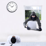 Thief stealing laptop in office. Male thief wearing mask and stealing a laptop in the office through a window when the employee is sleeping Royalty Free Stock Photo