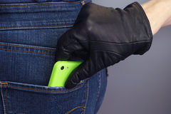 Thief stealing mobile phone from back pocket. Of a woman royalty free stock photography