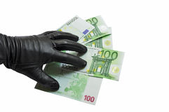 Thief stealing money. A thief stealing money with gloved hand, concept of bribery or financial theft stock photography