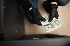 Thief stealing money from safe at crime scene. Theft, burglary and people concept - thief stealing money from safe at crime scene Royalty Free Stock Photos