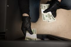 Thief stealing money from safe at crime scene. Theft, burglary and people concept - thief stealing money from safe at crime scene Royalty Free Stock Image