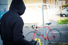 Thief stealing a parked bike in city street. Thief stealing a parked bike in the city street royalty free stock photo