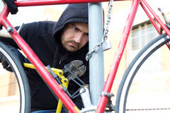 Thief stealing a parked bike in city street. Thief stealing a parked bike in the city street royalty free stock photography