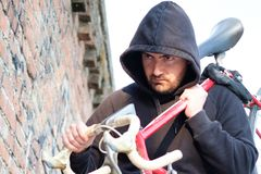 Thief stealing a bike in the city street. Thief stealing a parked bike in the city street Royalty Free Stock Photos