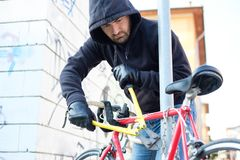 Thief stealing a bike in the city street. Thief stealing a parked bike in the city street royalty free stock image