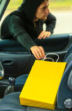 Thief stealing shopping bag from the car Royalty Free Stock Images