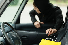 Thief stealing shopping bag from the car. Transportation, crime and ownership concept - thief stealing shopping bag from the car stock image