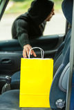Thief stealing shopping bag from the car Royalty Free Stock Photo
