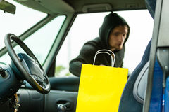 Thief stealing shopping bag from the car Stock Photos
