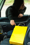 Thief stealing shopping bag from the car Royalty Free Stock Photos