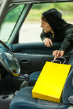 Thief stealing shopping bag from the car Royalty Free Stock Image