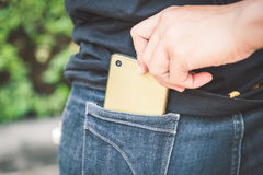 Thief is stealing smartphone from blue jeans pocket. Thief stealing the mobile phone from the blue jeans pocket of a woman royalty free stock photos