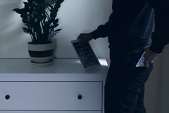 Thief stealing tablet. Thief in house stealing tablet and smartphone stock photos
