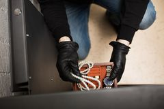 Thief stealing valuables from safe at crime scene. Theft, burglary and people concept - thief stealing valuables from safe at crime scene Royalty Free Stock Images