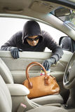 Thief stealing wallet from car. Thief stealing wallet in bag from car stock photos