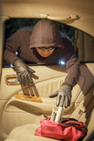 Thief stealing wallet from car. At parking lot royalty free stock photography