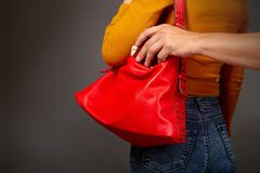 The thief steals from the bag. The robber comes up from the back to the girl secretly pulls out of her bag a purse with money stock images