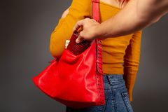 The thief steals from the bag. The robber comes up from the back to the girl secretly pulls out of her bag a purse with money stock photo