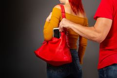 The thief steals from the bag. The robber coming up from the back to the girl secretly pulls her smartphone out of her bag stock image